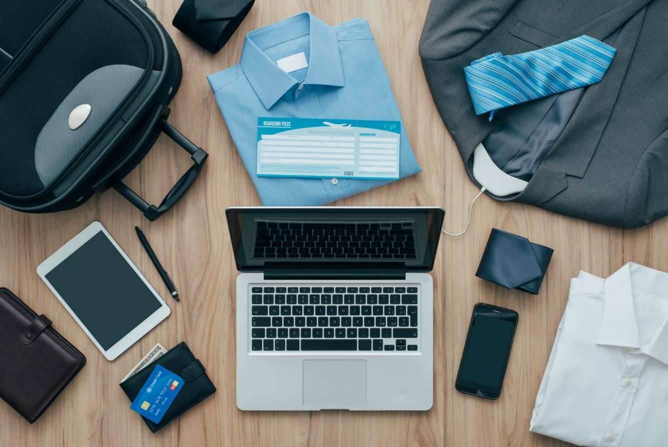 business traveller items such as laptop, mobile fine, shirt, and tie